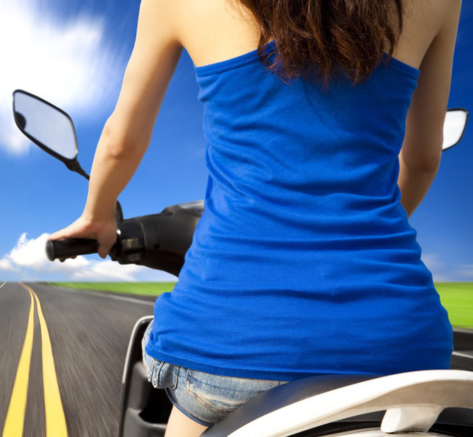 slim woman riding scooter with high speed on the road